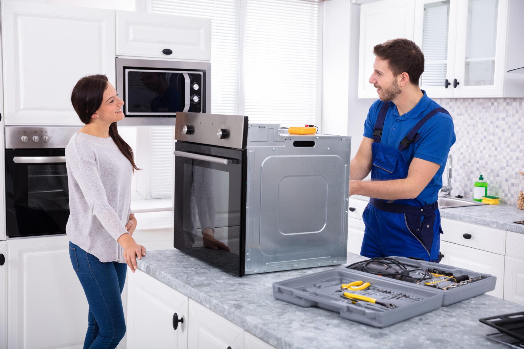 Young Repairman Repairing Oven On Kitchen Worktop