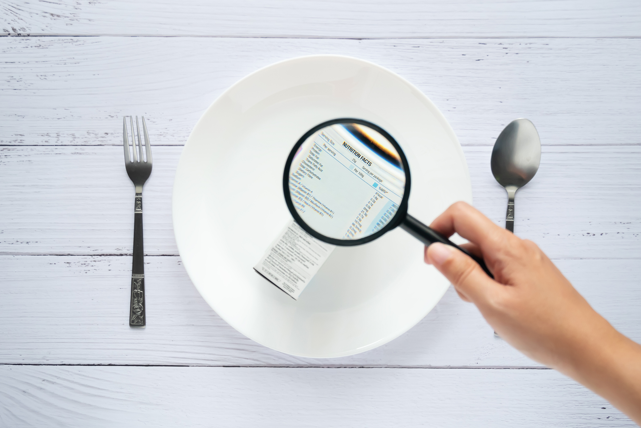 hand use the magnifying glass to zoom in to see the details of the nutrition facts label on the side of the consumer product box on white dish